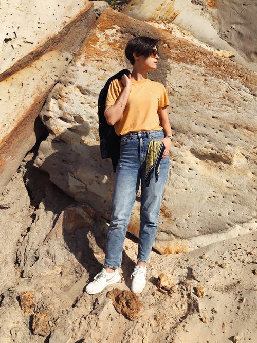 Woman in Orange Tank Top and Blue Denim Jeans Standing on Brown Rock Formation