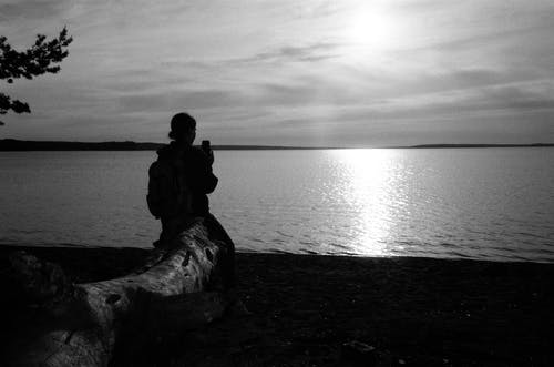 Grayscale Photo of Man and Woman Kissing on Seashore