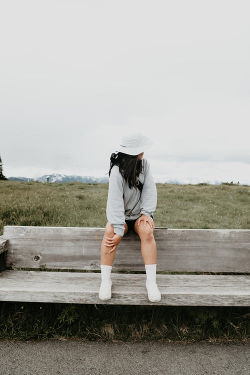 Young faceless woman sitting on wooden bench