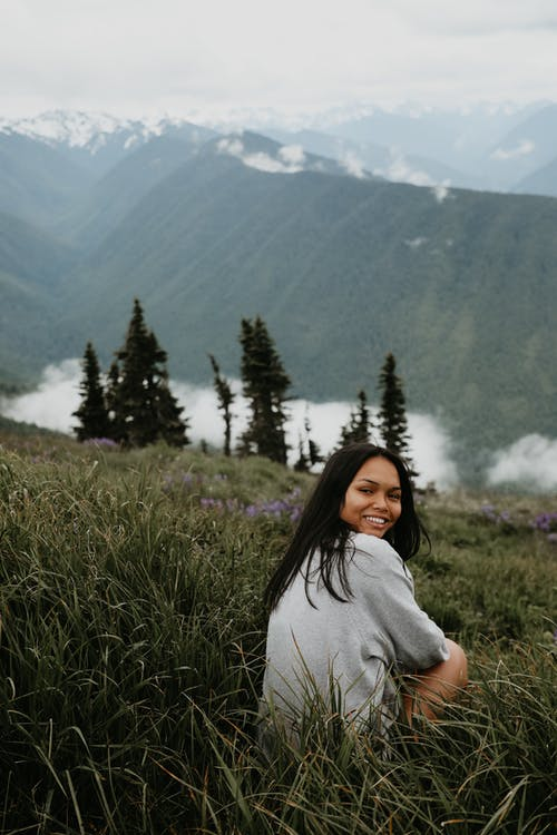 Young ethnic woman sitting on hill slope