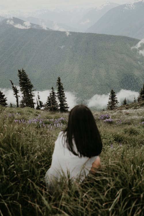 Back view of faceless female traveler sitting on grassy hill slope against mountains and clouds