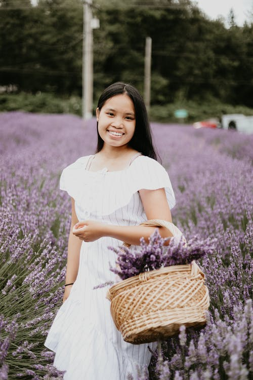 Cheerful Asian female in thin dress smiling and holding basket with fresh lavender flowers in meadow while looking at camera