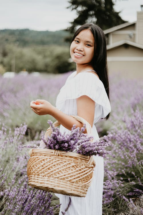 Happy Asian woman in blooming field