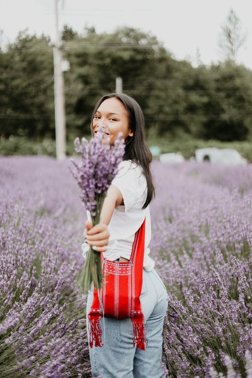 Young ethnic female smiling and raising hand with bunch of fresh lavenders  while looking at camera