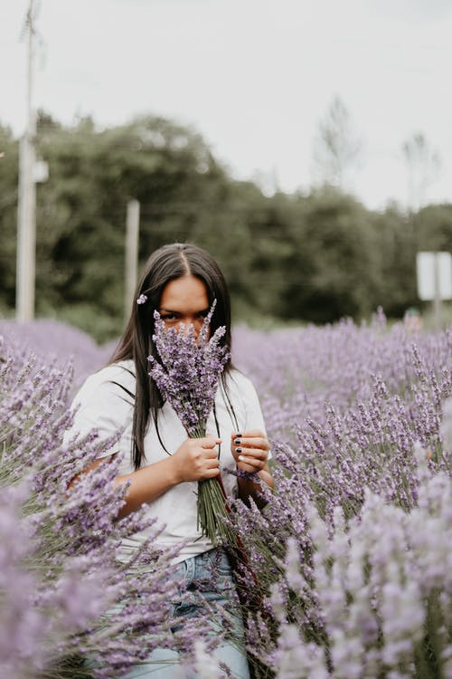 Woman with bouquet of flowers in lavender field