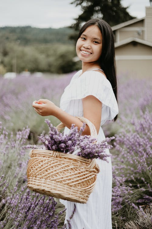 Side view of young Asian female with basket full of lavender flowers standing in meadow and looking at camera while smiling