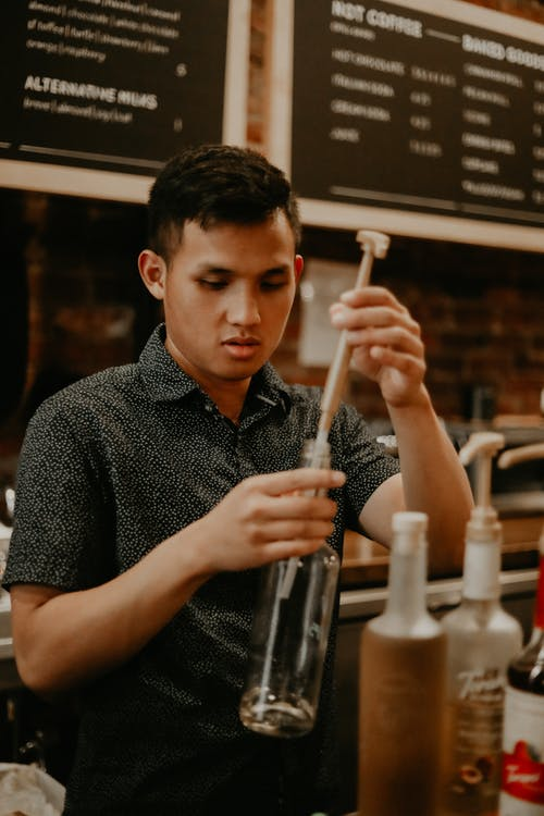 Concentrated ethnic male barista removing pump from syrup bottle while working in modern cafe
