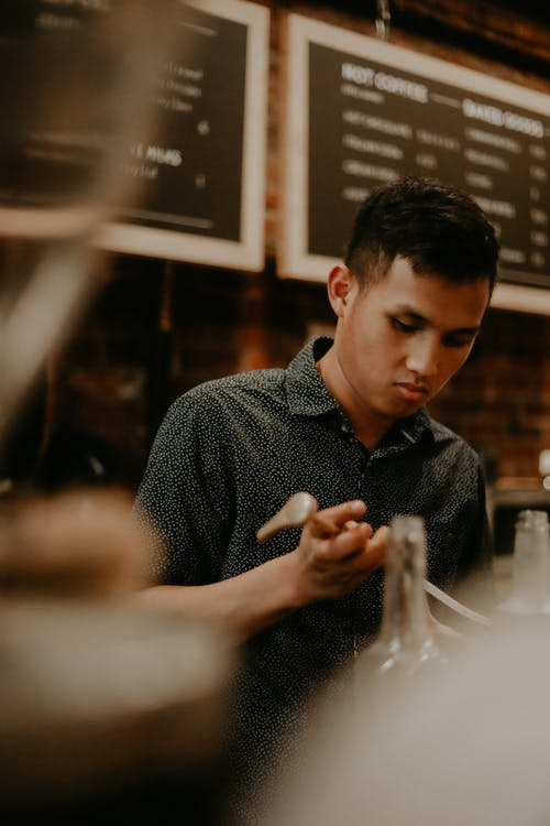 Focused male barista working at cafe counter