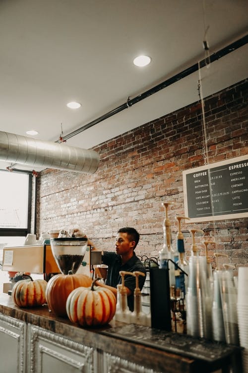 Focused young ethnic male barista preparing beverage while working at counter in modern cafe