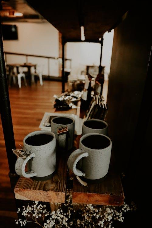 Ceramic mugs for sale placed on cafe shelf