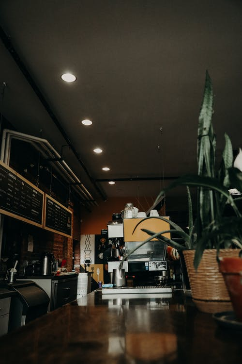 Interior of contemporary coffee house with long wooden counter with modern coffee machine and coffee making equipment