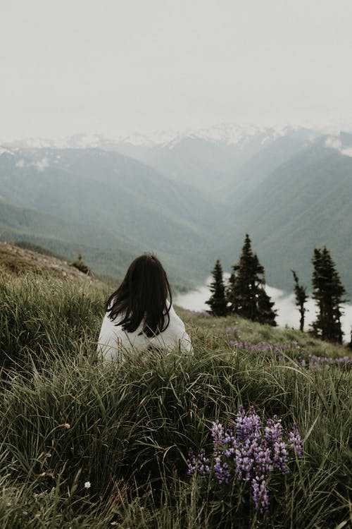 Unrecognizable woman sitting on hill and looking at majestic mountains