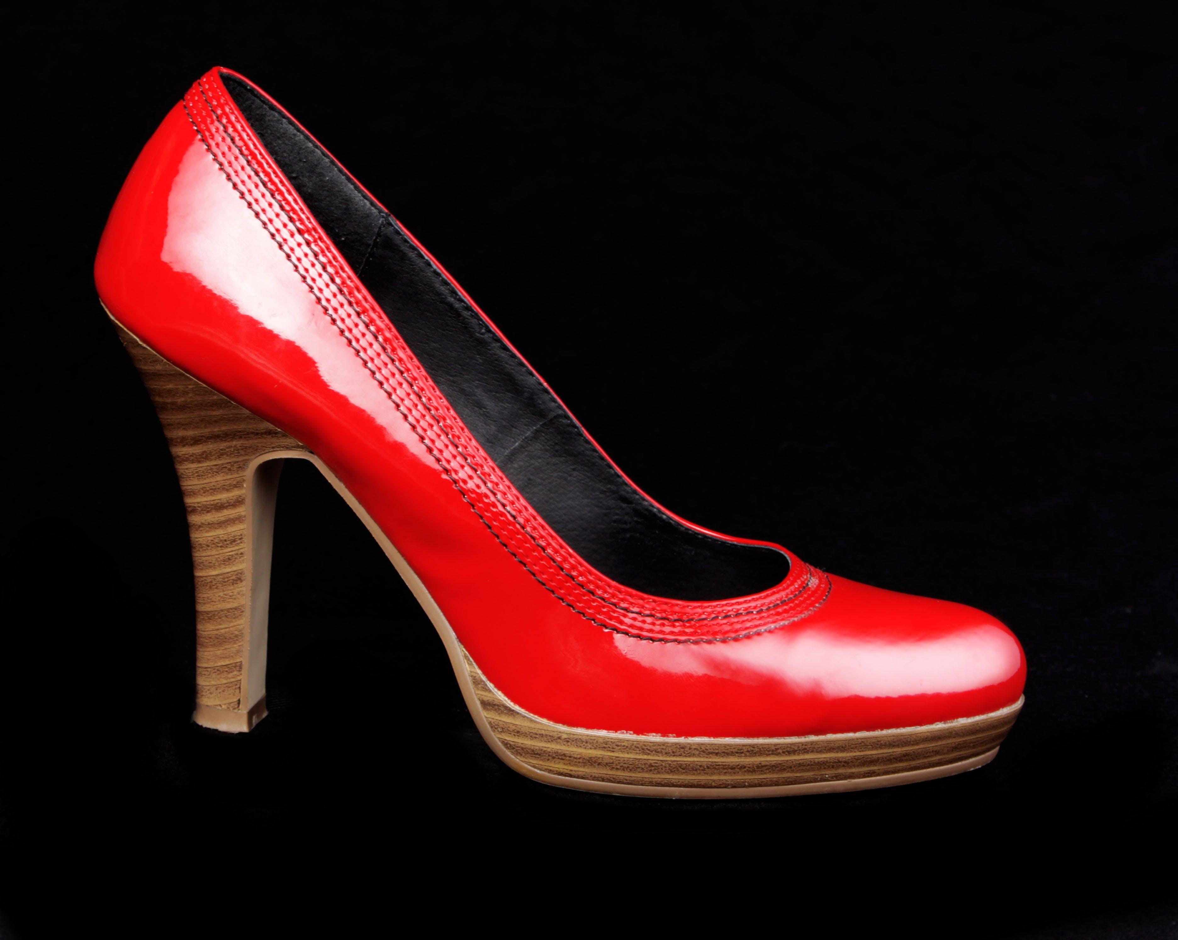 Unpaired Red Leather Platform Stacked Stilettos on Black Surface