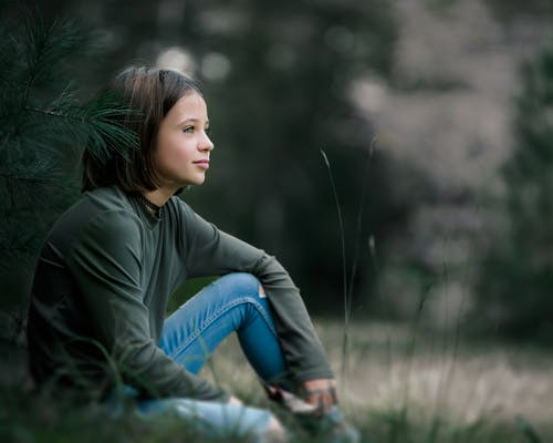Side view content preteen girl wearing casual outfit sitting on lush lawn in summer nature and looking away dreamily