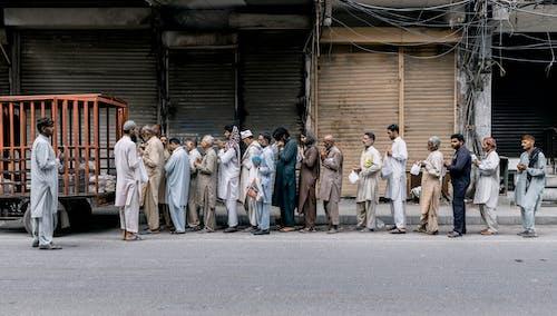 Group of People Standing on Gray Asphalt Road
