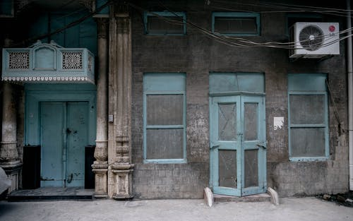 Blue Wooden Door on Brown Brick Building