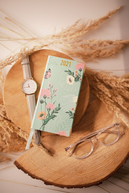 Composition of diary placed near watches and eyeglasses