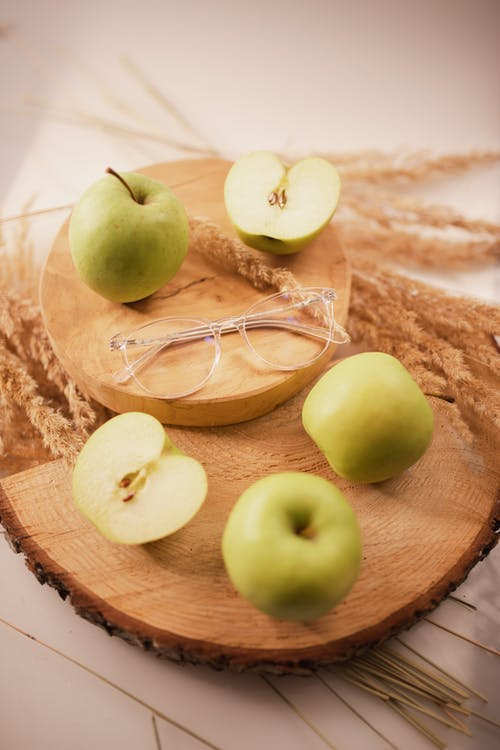 From above composition of whole and cut green organic apples arranged on wooden board with eyeglasses on center