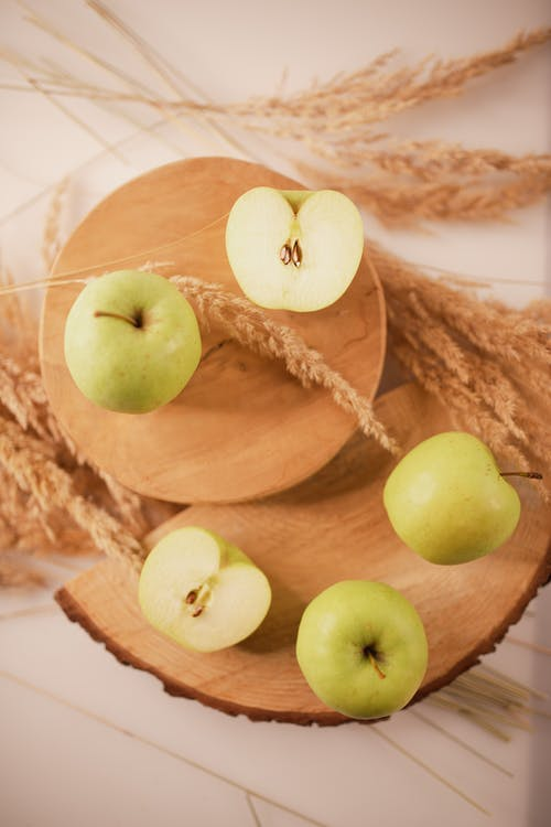 Green apples arranged on wooden boards with wheat spikes