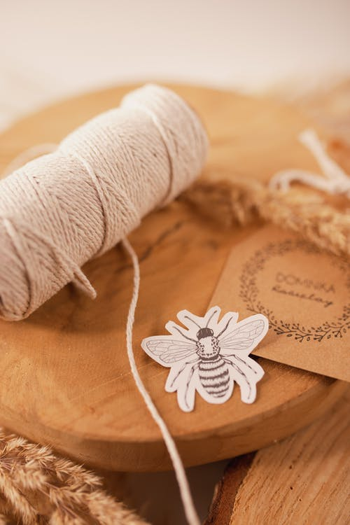 Wooden board with thread and bug applique work