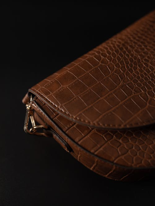 Brown leather purse on black background