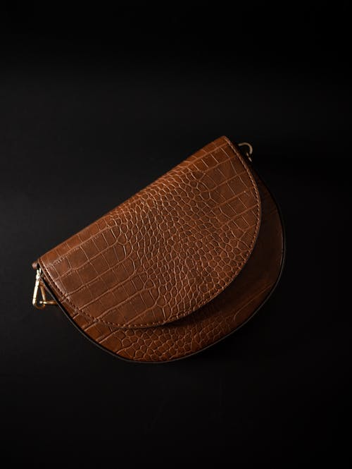 Trendy leather bag on black background