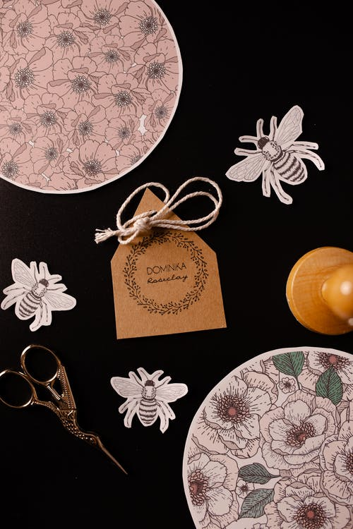 Top view composition of assorted decorative applique work ornaments and creative scissors surrounding card placed on black surface for handicraft