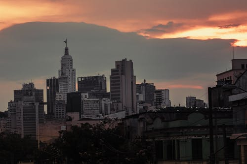 Contemporary city with skyscrapers and modern buildings under colorful cloudy sky at sundown