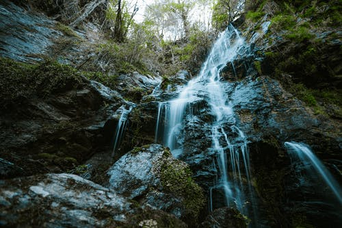 Tall cascade falling over mountain in forest