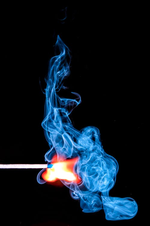 Lighted Match With Smoke on Black Background