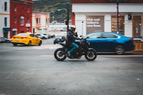Full body of anonymous male biker wearing helmet and driving motorcycle on asphalt road with cars near residential buildings on street