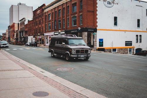 Black minivan driving on asphalt road
