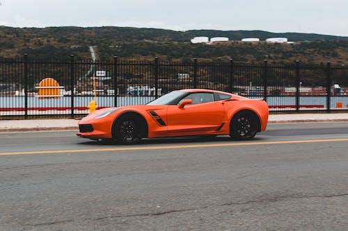 Orange modern car riding along metal fence