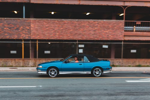 Side view of old timer blue cabriolet riding on highway near construction with brick wall on street in city outside