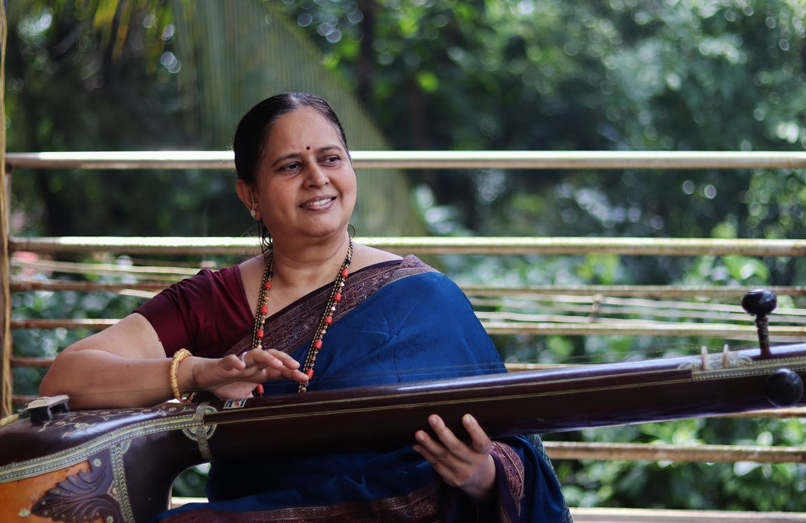 Woman in Brown and Blue Sari Sitting on Brown Wooden Bench