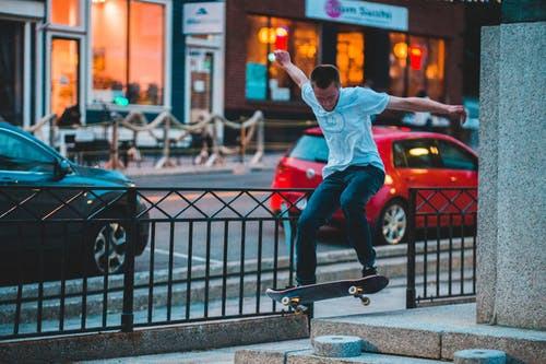 Male athlete with raised arms performing trick on skateboard in air near roadway in town