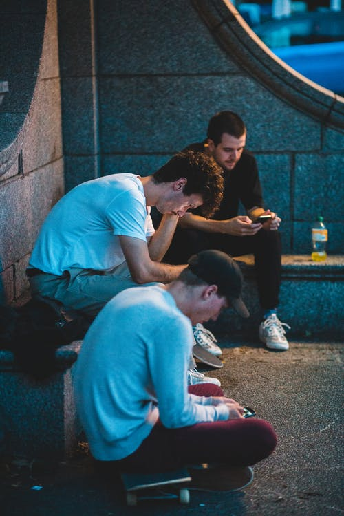 Young men text messaging on cellphones while sitting on skateboards near stone monument in night city