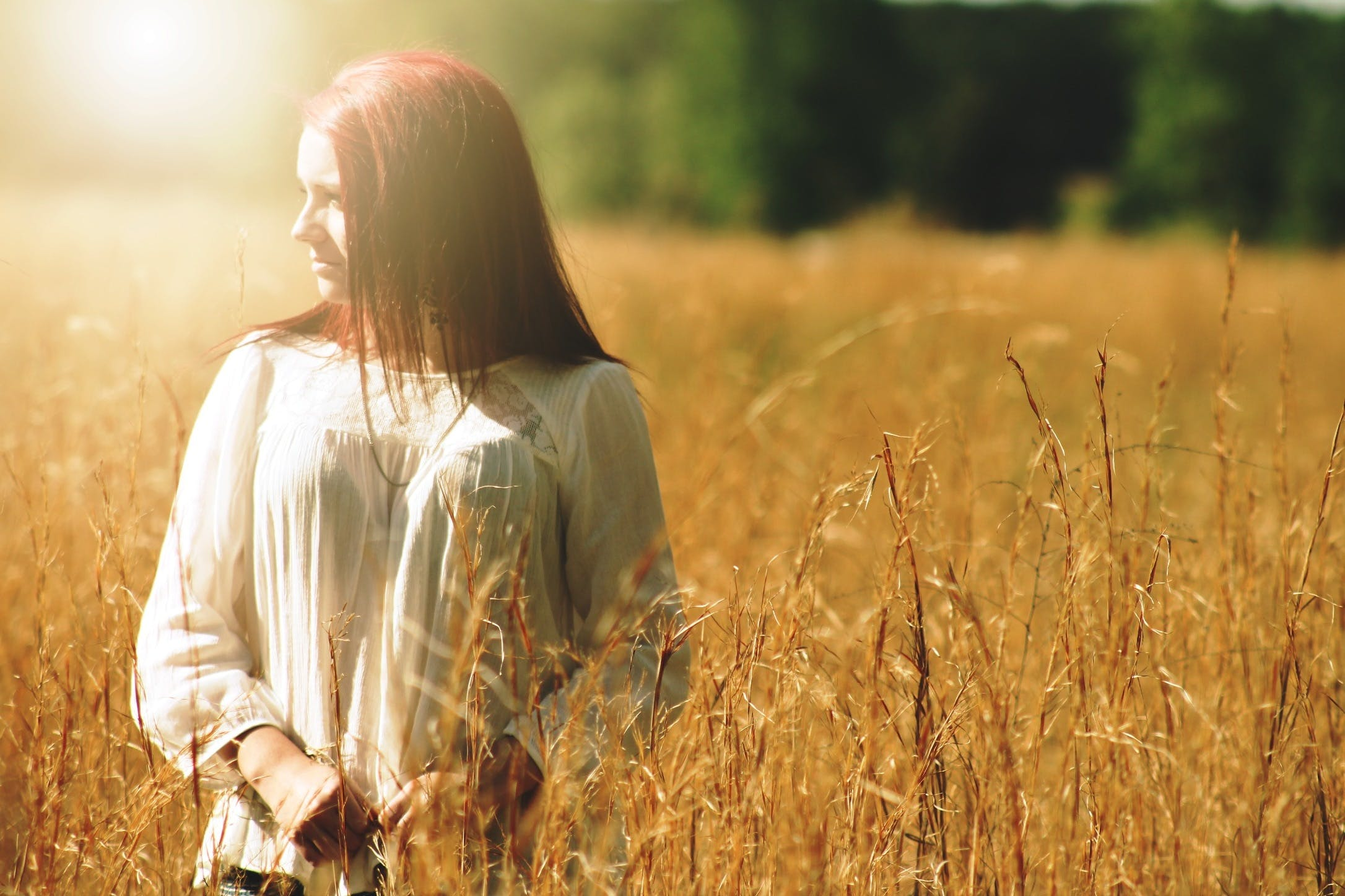 Woman Wearing White Long Sleeved Shirt Standing in Brown Grass Field