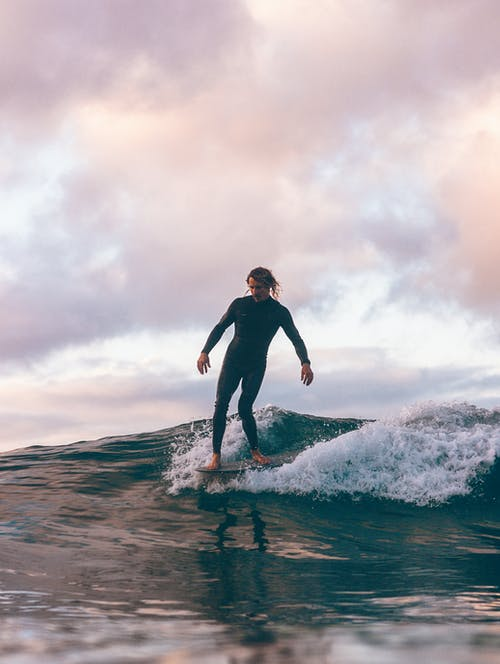 Woman in Black Long Sleeve Shirt and Black Pants Surfing on Sea Waves