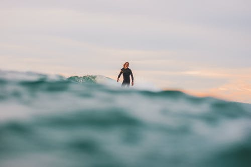 Woman in Black Wetsuit Surfing on Sea Waves