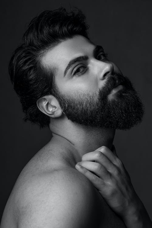 Bearded man with trendy hairstyle touching neck