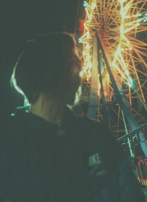 Man in Black Shirt Standing Near Ferris Wheel during Night Time