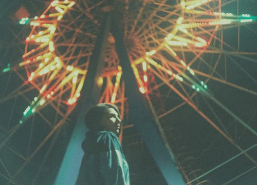 Man in Black Jacket Standing Near Ferris Wheel during Night Time