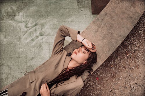 Woman in Brown Long Sleeve Shirt Lying on Brown Concrete Floor