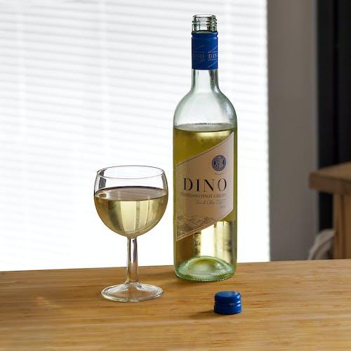 Green Wine Bottle Beside Clear Wine Glass on Brown Wooden Table