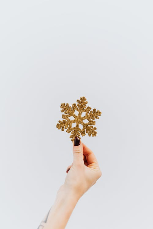 Person Holding Golden Snowflake