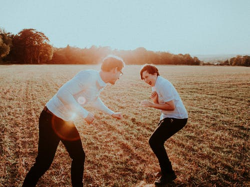 Side view of teen boy with father having fun and playing in field at sunset