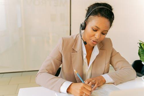 Woman In Beige Blazer Writing On White Paper