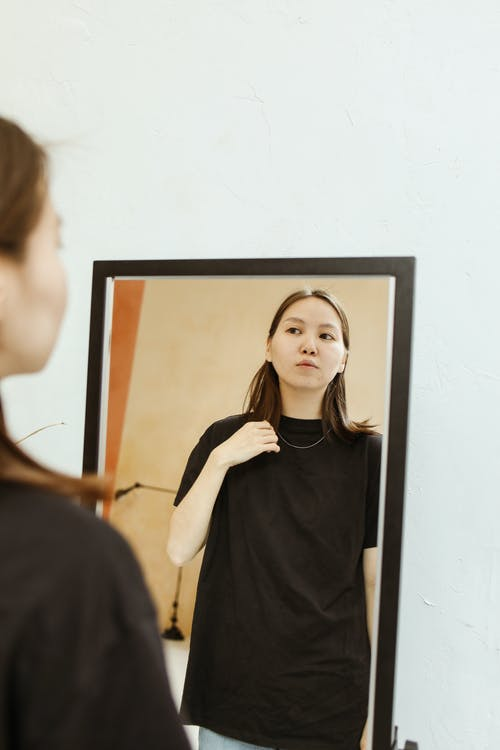 A Woman Looking Herself on a Mirror
