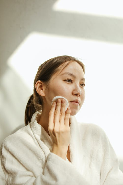 A Woman Wiping Her Face with a Cotton Pad